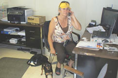 Shirley Bays speaks on the phone with a customer at West Virginia Land, Farm, Home Realty with the company of her Miniature Pincher Trixie.