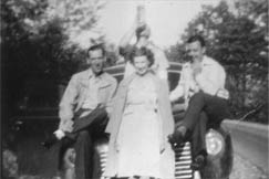 Perched on their Plymouth, the young Mrs. Morris sits with Audry Morris (left), her husband's brother, Roy Morris (right), her husband's cousin, and an unidentified man (rear).