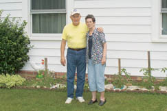 """Nina Knight and husband Orville """"Bud"""" Knight are standing in front of their tomato patch."""
