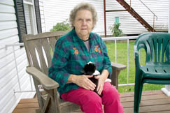 "Retired Postmaster Marva Sutton enjoys sitting on her porch with her kitten ""Michelle""."