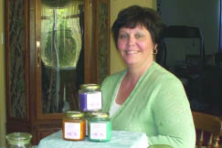 Neketa McLaughlin of Scented Wonders displays candles in a few of their 100 fragrances